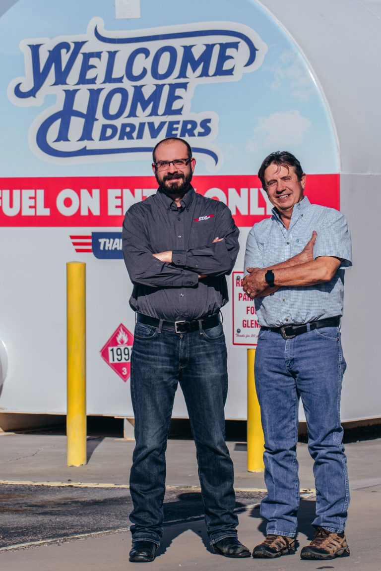 Two members of our team at DSW truck driving smiling in front of a sign that says 'Welcome Home Drivers'